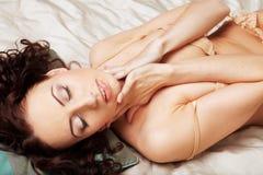 Junge Frau des sexy Brunette, die beige Wäsche trägt Stockfoto
