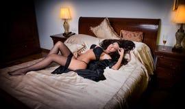 junge Frau des sexy Brunette, die schwarze Wäsche im Bett trägt Stockbild