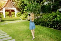 Junge Frau des Sonnenscheins, die Foto mit Tablette macht und auf grünen Palmen und Haushintergrund in Thailand lächelt Lizenzfreies Stockbild