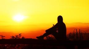 Junge Frau des Sonnenuntergangschattenbildes, die traurigen schauenden Sonnenuntergang feeing ist Stockfoto