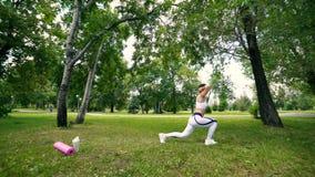 Junge Frau des Sports ist die Ausbildung und tut zur Schau trägt im Park Eignungsmädchen, das Laufleinen im Park am Sommer tut stock footage