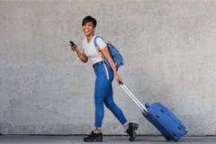Junge Frau des vollen Körpers, die mit Reisetasche und -Handy geht lizenzfreie stockfotos