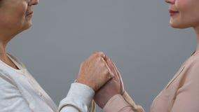 Junge Frau, die ältere weibliche Hände, Sozialunterstützung zu den Pensionären, Wohlfahrt hält stock video