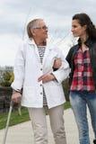 Junge Frau, die älterer Person hilft Stockfoto