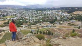 Junge Frau, die über Alexandra, zentrales Otago, Neuseeland schaut stockfotos