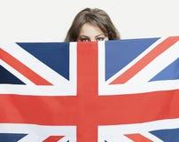 Junge Frau, die über britische Flagge gegen grauen Hintergrund späht lizenzfreie stockfotos