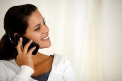 Junge Frau, die über das Mobiltelefon nach links schaut spricht Stockfotos