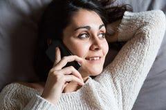 Junge Frau, die über das Telefon und das Lächeln spricht Lizenzfreies Stockfoto