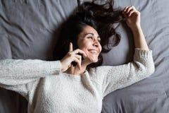 Junge Frau, die über das Telefon und das Lächeln spricht Lizenzfreie Stockfotos