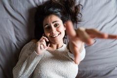 Junge Frau, die über das Telefon und das Lächeln spricht Stockfotos