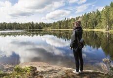 Junge Frau, die über dem See schaut lizenzfreies stockbild