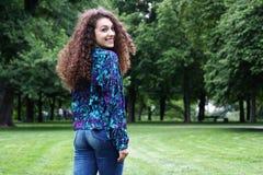Junge Frau, die über ihrer Schulter schaut Stockfotos