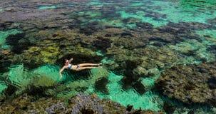 Junge Frau, die über Korallenriff auf einer Tropeninsel schwimmt stock video