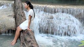 Junge Frau, die über Wasserfall sitzt stock video footage