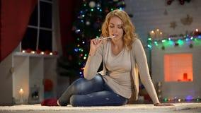 Junge Frau, die über wishlist, Schreibensbuchstabe zu Sankt auf Weihnachtsabend denkt stockfotos