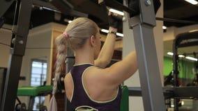 Junge Frau, die Übung in der Maschine in der modernen Turnhalle tut stock video