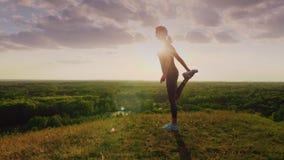 Junge Frau, die Übung in einem epischen schönen Platz bei Sonnenuntergang ausdehnend tut Schöner greller Glanz von der Sonne, die stock video footage