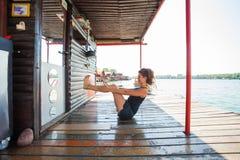 Junge Frau, die Übung für die Bauchmuskeln im Freien durch tut Stockfotos