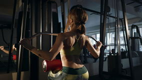 Junge Frau, die Übung für Rückseite auf Trainingsmaschine tut stock footage