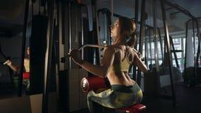 Junge Frau, die Übung für Rückseite auf Trainingsmaschine tut stock video footage
