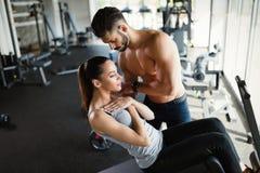 Junge Frau, die Übungen für ABS mit persönlichem Trainer tut Lizenzfreies Stockfoto