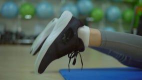 Junge Frau, die Übungen für die Rückseite auf einer Eignungsmatte tut Gymnastik stock video