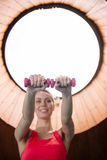 Junge Frau, die Übungen mit Gewichten in der Turnhalle tut Stockbild
