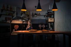 Junge Frau, die Abendessen in der modernen Hauptküche vorbereitet stockfotos