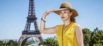 Junge Frau, die Abstand gegen Eiffelturm in Paris untersucht Stockbild