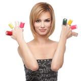 Junge Frau, die acht Flaschen Nagellack zeigt Stockfotos