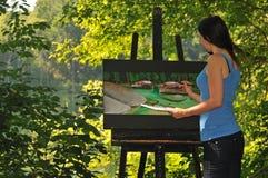 Junge Frau, die Acrylszene auf Segeltuch malt Lizenzfreie Stockfotos
