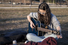 Junge Frau, die Akustikgitarre an der Dämmerung abstimmt Stockfotografie
