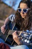 Junge Frau, die Akustikgitarre an der Dämmerung spielt Stockbild