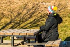 Junge Frau, die allein auf einer Bank sitzt Lizenzfreie Stockfotos