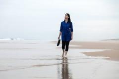 Junge Frau, die allein in einen einsamen Strand geht Lizenzfreies Stockbild
