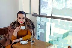 Junge Frau, die allein im Café - Kaffeepause sitzt Stockfotos