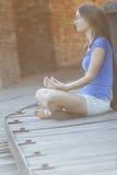 Junge Frau, die allein meditiert lizenzfreie stockbilder