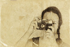 Junge Frau, die alte Kamera hält gefiltertes Bild, im altem Stil Foto lizenzfreie stockbilder