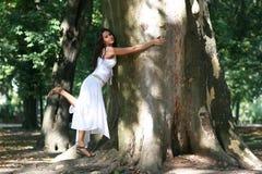 Junge Frau, die alten Baum umarmt Stockfoto