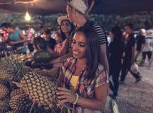 Junge Frau, die Ananas auf tropischem Straßenmarkt- im glücklichen lächelnden Mädchen-Touristen Thailands kauft frische Früchte w Lizenzfreie Stockbilder
