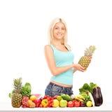 Junge Frau, die Ananas hinter Tabelle voll von den Früchten und von VE hält Stockfotografie