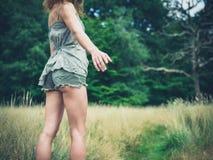 Junge Frau, die in Angebothand der Wiese steht Lizenzfreies Stockfoto