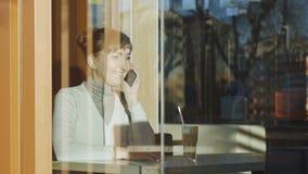 Junge Frau, die Anruftelefon im Café herstellt Porträt der kaukasischen Frau mit Spitzewollschal nennt auf ihrem smarphone Lächel stock video footage