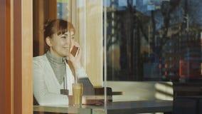 Junge Frau, die Anruftelefon im Café herstellt Porträt der kaukasischen Frau mit Spitzewollschal nennt auf ihrem smarphone Lächel stock footage