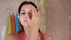 Junge Frau, die Antifaltencreme aufträgt Schönes Mädchen setzt Creme auf das Gesicht in das Badezimmer ein Attraktive junge Frau stock video
