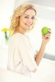 Junge Frau, die Apfel in der Küche isst Stockbild