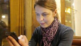 Junge Frau, die APP an einem Telefon verwendet und Kaffee und lächelnd im Café trinkt 4k UHD stock video footage