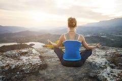 Junge Frau, die in asana Position auf einem Felsen sitzt Stockfotos