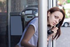 Junge Frau, die außerhalb der Telefonzelle schaut Lizenzfreie Stockbilder