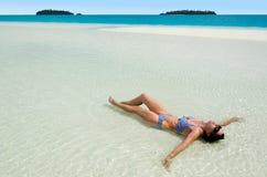 Junge Frau, die auf Aitutaki-Lagunen-Koch Islands sich bräunt Stockfotos